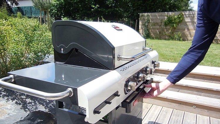 Mężczyzna otwiera grill gazowy znajdujący się ogrodzie.